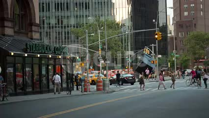 Starbucks Coffee House and famous cube sculpture on Cooper Square in Greenwich Village in summer during day, taxicab turning corner, Manhattan NYC
