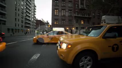taxi cabs on Lower 5th ave on cloudy day - stationary shot in NYC