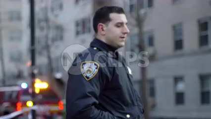 NYPD police officer at crime scene with fire truck in background - closeup in 1080 HD and 4K NYC