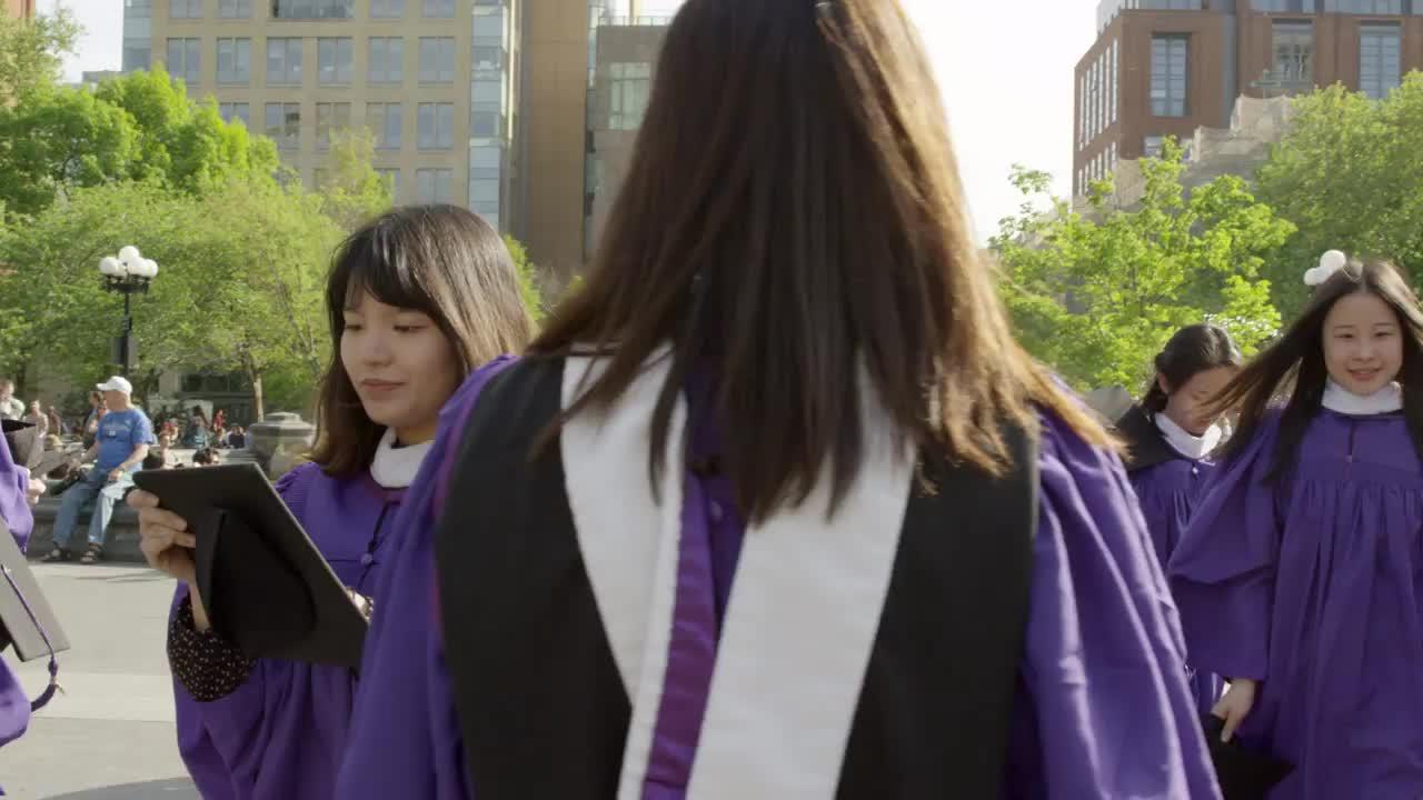 young women in purple NYU cap and gown - graduates in Washington ...