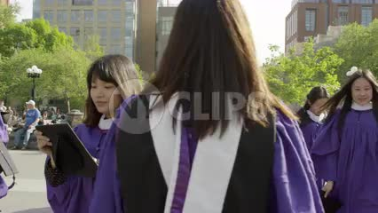 young women in purple NYU cap and gown - graduates in Washington Square Park - Asian girls graduating college in NYC