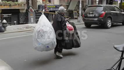 woman carrying garbage bags filled with empty soda cans in Greenwich Village