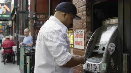 man swiping credit or debit card in ATM machine on Macdougal Street in Greenwich Village