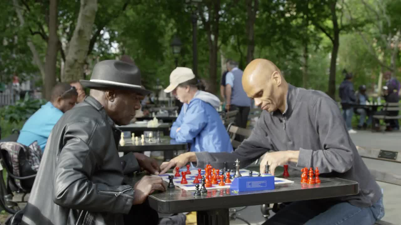 two men playing chess at tables in Washington Square Park in Spring -  masters hitting timer and making moves in 1080 and 4K NYC