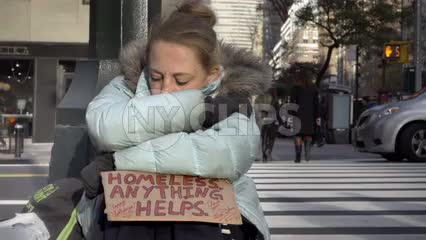 homeless woman on cold winter day with help sign in street - Park Avenue with Met-Life Building and crosswalk in 1080 HD NYC
