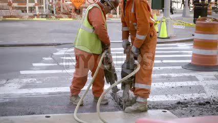construction workers in orange suits drilling into concrete in slow motion - 1080 HD in NYC