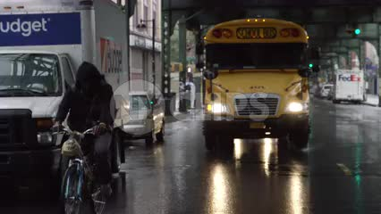 man riding bicycle with yellow school bus driving in rain under bridge in Brooklyn in slow motion