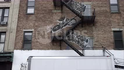 truck driving by graffiti on building with fire escape in gritty urban area