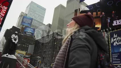 pretty blond twins looking up at ads and billboards - snowing in Times Square NYC