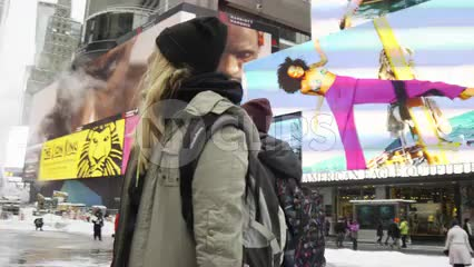 gorgeous blonde tourists looking around Times Square in awe in the snow - snowing in Manhattan morning in NYC