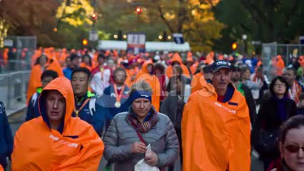 crowd in orange ponchos after Marathon walking out of Central Park 1080 HD in NYC