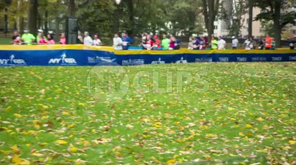 far shot of leaves on ground - green grass and trees with Marathon runners in background in Central Park in spring 1080 HD in NYC