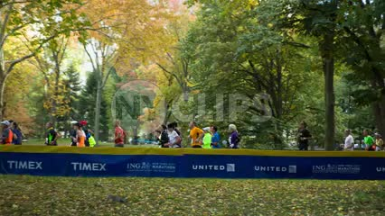 far shot of marathon runners in Central Park in spring with beautiful colorful changing leaves on trees 1080 HD in NYC