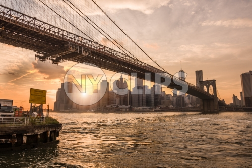 Brooklyn Bridge and Manhattan skyline from across East River at sunset in NYC
