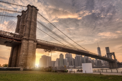 Brooklyn Bridge Park with Manhattan skyline across East River and beautiful orange sunset in NYC
