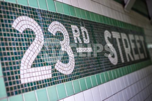23rd st sign on subway station wall in NYC