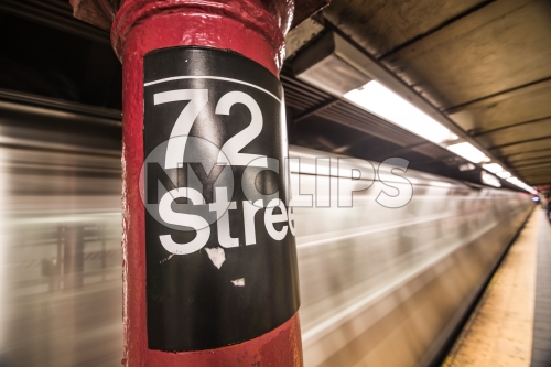 72nd street subway sign on platform pillar with blurred motion train entering station in NYC