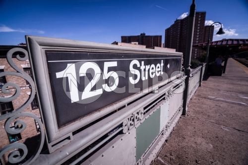 125th street sign in Uptown Manhattan with projects in background in NYC