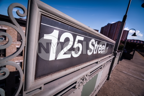 125th street sign at elevated subway station platform and project housing in Uptown Manhattan NYC