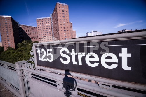 125th street subway sign in Harlem with housing projects in background in Uptown Manhattan NYC