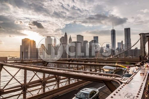 view of Manhattan skyline with skyscrapers and Freedom Tower from Brooklyn Bridge at sunset in NYC