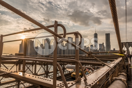 steel beams of Brooklyn Bridge close-up with Manhattan skyline in background at sunset in NYC