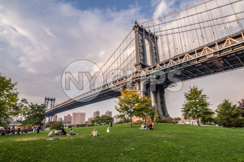 Manhattan Bridge and people lying on green grass of Brooklyn Bridge Park on summer day in NYC