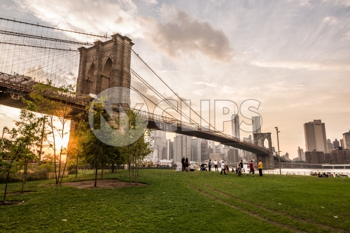 people watching sunset and Manhattan skyline from Brooklyn Bridge Park in NYC