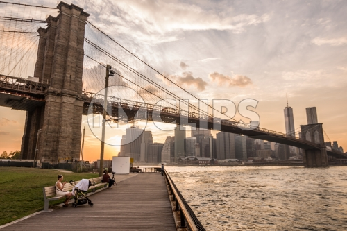 people on benches in Brooklyn Bridge Park enjoying summer view of Manhattan skyline and East River water at sunset in NYC