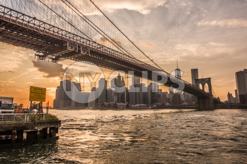 Brooklyn Bridge and East River with Manhattan skyline in background at sunset with beautiful orange sky in NYC