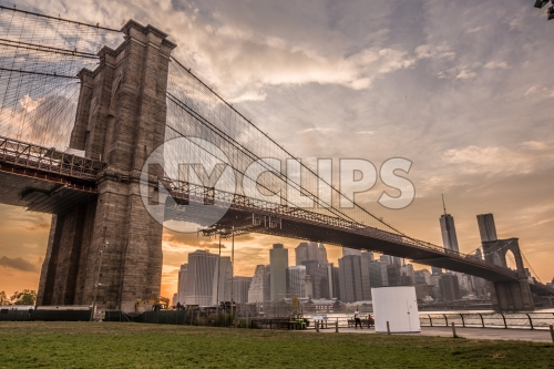 Brooklyn Bridge and Manhattan skyline during the day - beautiful orange sky at sunset in NYC