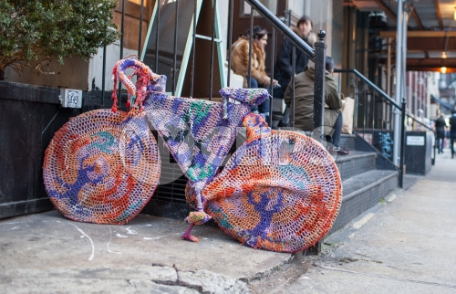 hipsters sitting on stoop with bicycle sweater parked on Lower East Side of Manhattan on fall day in NYC