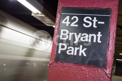 subway column sign for 42nd st and Bryant Park on platform with motion blur train leaving station