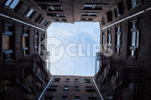 upward angle from city courtyard between 4 buildings looking up at sky