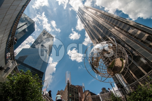 famous globe sculpture and Trump International Tower and Hotel viewed from upward angle from subway station at Columbus Circle on sunny day with bright blue sky