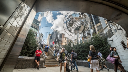 Columbus Circle with famous globe sculpture and people in Midtown Manhattan on sunny summer day from subway station stairs in NYC
