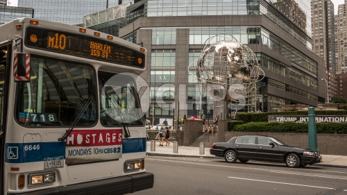 bus stop at Columbus Circle with famous globe sculpture and people in Midtown Manhattan on sunny summer day in NYC