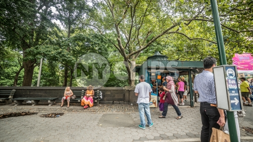 Columbus Circle with people in Midtown Manhattan on sunny summer day across the street from Central Park, trees with green leaves in NYC