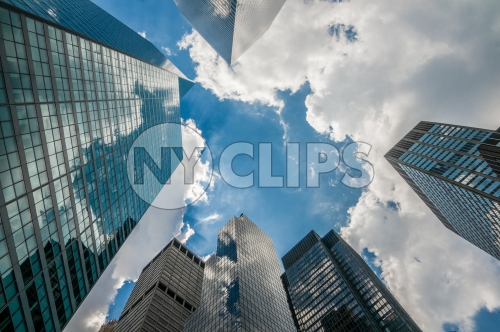 corporate office buildings - upward angle of glass window skyscrapers over blue sky on sunny summer day in Manhattan