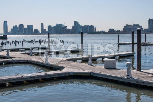 dock on East River with wood dowels and view of Queens in late afternoon day