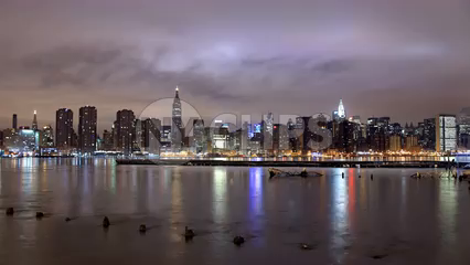 beautiful nighttime skyline timelapse of Manhattan skyscrapers with East River water reflections of lights in 4K