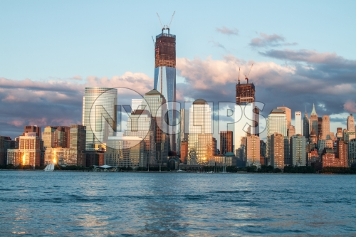 Freedom Tower under construction in Manhattan skyline in early evening from across East River water