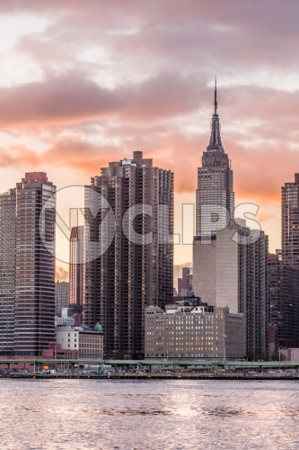 Empire State Building and skyscrapers in HDR at sunset from across East River water waves in Manhattan