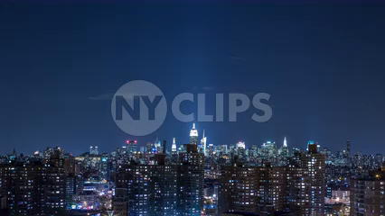 nighttime timelapse of Manhattan skyline with Empire State Building and clouds floating by - 4K at night