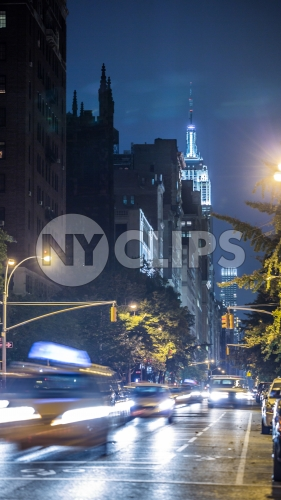 Empire State Building with blur motion taxi cabs driving down Lower Fifth Ave at night in Manhattan