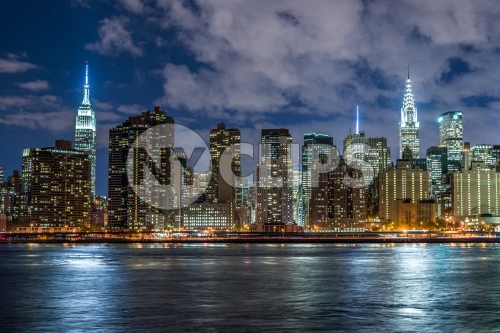 Empire State Building and Chrysler famous skyscrapers in Manhattan skyline from across East River water at night