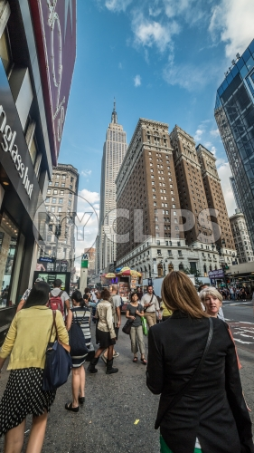 Empire State Building towering over 34th street and Herald Square on crowded busy street on summer day in Manhattan