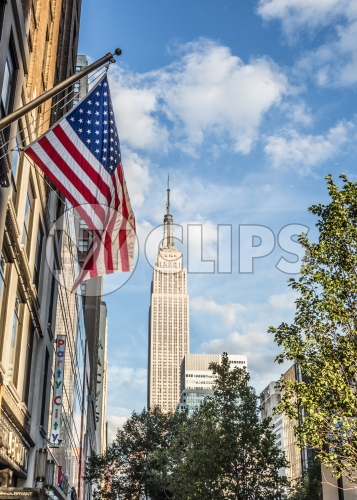 American flag and Empire State Building on beautiful colorful sunny summer blue sky day in Manhattan NYC