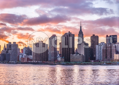 Manhattan skyline with Empire State Building from across East River in colorful HDR sunset