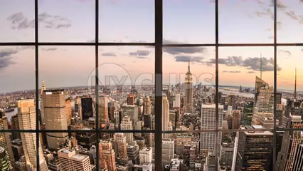 Manhattan cityscape view of Empire State Building tilting down from interior window terrace - 4K at sunset